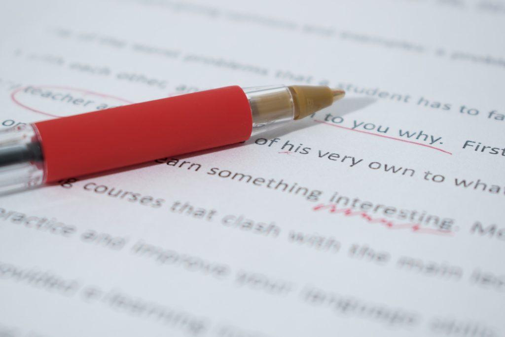 Image d'illustration montrant en gros plan une copie en cours de correction avec des annotations en rouge et un stylo rouge posé négligemment dessus.
